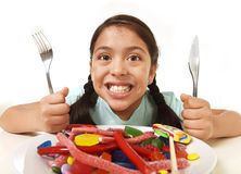 Happy excited Latin female child holding fork and knife sitting at table ready for eat a dish full of candy Stock Images
