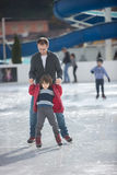 Happy excited little boy and his young father learning ice-skati Royalty Free Stock Image