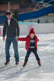Happy excited little boy and his young father learning ice-skati Royalty Free Stock Photo