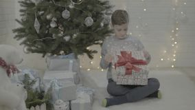 Happy excited little boy opening christmas present gift box in decorated new year tree festive atmosphere room stock video footage