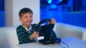 Happy excited little boy playing videogame with racing wheel. Professional shot in 4K resolution. 093. You can use it e.g. in your commercial video, business Royalty Free Stock Images