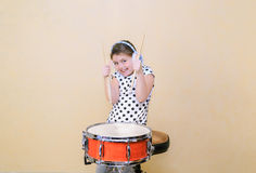 Happy excited little girl in motion sitting behind a snare drum Stock Images