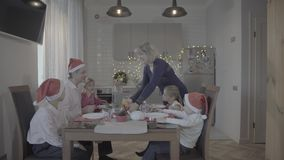 Happy excited lovely family of six celebrating Christmas dinner in festive atmosphere cozy kitchen stock footage