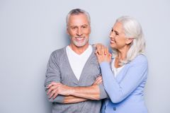Happy excited lovely tender gentle cute elderly people are smiling and embracing, isolated on grey background royalty free stock image
