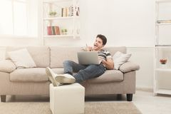 Happy man win. Winner, young man with laptop. Happy excited man celebrate his success. Winner, young man reading on laptop at home, copy space Royalty Free Stock Images