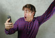 Happy and excited man celebrating success making money online gambling with mobile phone winning internet bet isolated grunge. Natural portrait of young crazy stock image