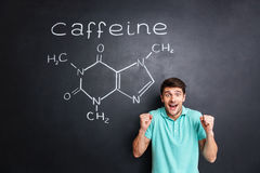 Happy excited man celebrating success over drawn caffeine molecule structure Royalty Free Stock Photography
