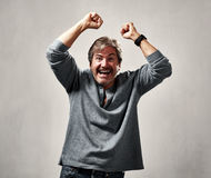 Happy excited man. Glad excited laughing mature man expressions over gray background Stock Photography