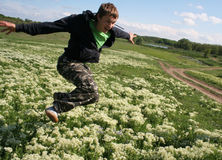 Happy excited man jump high. Inspired guy flying in the field of Royalty Free Stock Photo