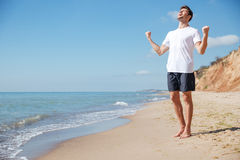 Happy excited man with raised hands celebrating success on beach Royalty Free Stock Photos