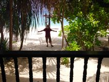 Happy excited man standing front beachfront chalet tropical island resort Stock Image