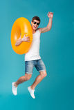 Happy excited man in sunglasses holding inflatable ring and jumping. Full length portrait of a happy excited man in sunglasses holding inflatable ring and Royalty Free Stock Photography