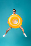 Happy excited man in sunglasses holding inflatable ring and jumping. Full length portrait of a joyful happy guy in sunglasses holding inflatable ring and jumping Royalty Free Stock Image