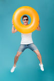 Happy excited man in sunglasses holding inflatable ring and jumping. Full length portrait of a joyful happy guy in sunglasses jumping and looking through Royalty Free Stock Photos