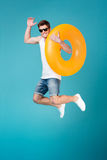 Happy excited man in sunglasses holding inflatable ring and jumping. Full length portrait of a smiling cheerful man in sunglasses holding inflatable ring and Stock Images