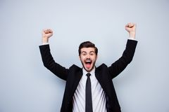 Happy excited man triumphing with raised fists on gray background stock image