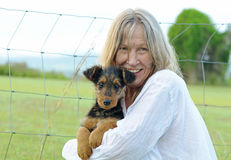 Happy excited mature woman smiles cuddling new baby puppy Royalty Free Stock Images