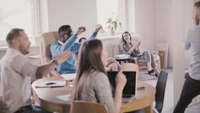 Happy excited multiethnic office workers celebrate success together with team leader in modern coworking slow motion. stock video
