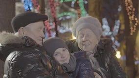Happy excited old married couple grandparent hug grandchild boy grandson in christmas light festive illumination evening stock video
