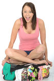Happy Excited Overwhelmed Young Woman Sitting on an Overflowing Suitcase Cross Legged Royalty Free Stock Photography