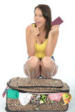 Happy Excited Pleased Young Woman Kneeling Behind a Suitcase Holding a Passport Stock Photography