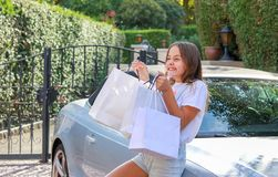 Happy excited preteen girl holding shopping bags staying near car smiling and enjoying presents and gifts. royalty free stock photo