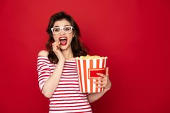 Happy excited pretty brunette lady eating pop corn stock photo