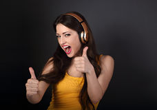 Happy excited shouting woman listening the music wireless earpho Stock Photography