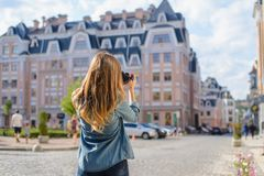 Happy, excited, stylish young woman taking photo of landmark in new old beautiful euripean city rear back behind close up view pho royalty free stock photography