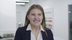 Happy excited successful businesswoman triumphing in office. The young woman happy about good news, motivated by great stock video