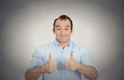 Happy, excited surprised young man showing thumbs up. Closeup portrait super happy, excited surprised young man in blue shirt showing thumbs up sign gesture stock photo