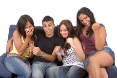Happy excited teens!. Three young woman and a man are sitting on a blue couch and looks like watching TV. They are very excited by what they see - over a white Stock Images