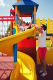 Happy excited toddler baby boy sliding in colorful playground at summer day with the help of father. Happy excited toddler baby boy sliding in colorful Royalty Free Stock Photo