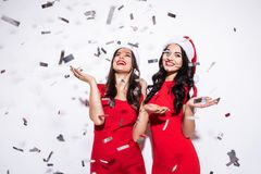 Happy excited two young women in santa claus hat dancing and laughing on confetti over white background Royalty Free Stock Photography