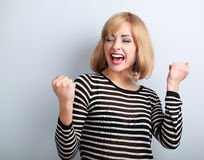 Happy excited winner with opened mouth. Happy blond young satisf. Acted woman showing the gesture by fists on blue background Royalty Free Stock Images