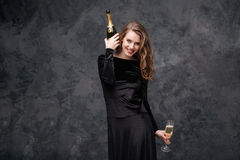 Happy excited woman with bottle and glass of champagne Stock Photography