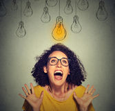 Happy excited woman in glasses looking up at bright light idea bulb above head Royalty Free Stock Photography