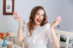 Happy excited woman holding two heart shaped cookies in cafe Royalty Free Stock Images