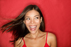 Happy excited woman looking. To the side screaming cheerful with wind in the hair on red background. Beautiful multiracial Asian Caucasian female model Royalty Free Stock Image