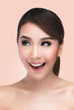 Happy excited woman looking to the side cheerful, Perfect Fresh. Skin on pink background with clipping path.  Beautiful Asian female model Royalty Free Stock Photos