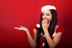 Happy excited woman in santa claus clothing holding and advertis Royalty Free Stock Images