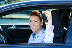 Happy, excited woman showing keys from her new car. Closeup portrait happy, smiling, young, attractive woman, buyer sitting in her new black car showing keys Royalty Free Stock Photo