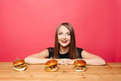 Happy excited woman smiling at camera with burgers on table in front of her. Royalty Free Stock Photo