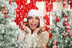 Happy and excited woman on snowfall background Christmas tree Stock Images
