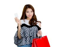 Happy excited woman standing and holding colorful shopping bags and finger point something isolated Stock Photography