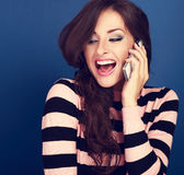 Happy excited woman talking on mobile phone with wide opened mou Stock Images