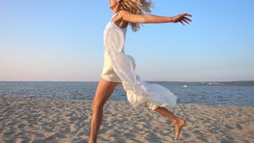 Happy excited woman running and jumping on the beach in slow motion. Happy excited woman in white dress running and jumping on the beach in slow motion stock video
