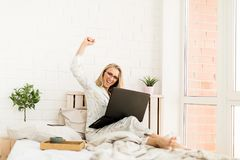 Happy excited woman working on a laptop at home.  Royalty Free Stock Photography
