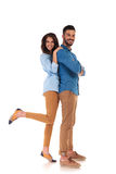 Oman leaning on her man and holding one leg up. Happy excited women leaning on her men and holding one leg up on white background stock image