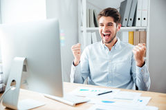 Happy excited young businessman sitting and celebrating success Stock Photos